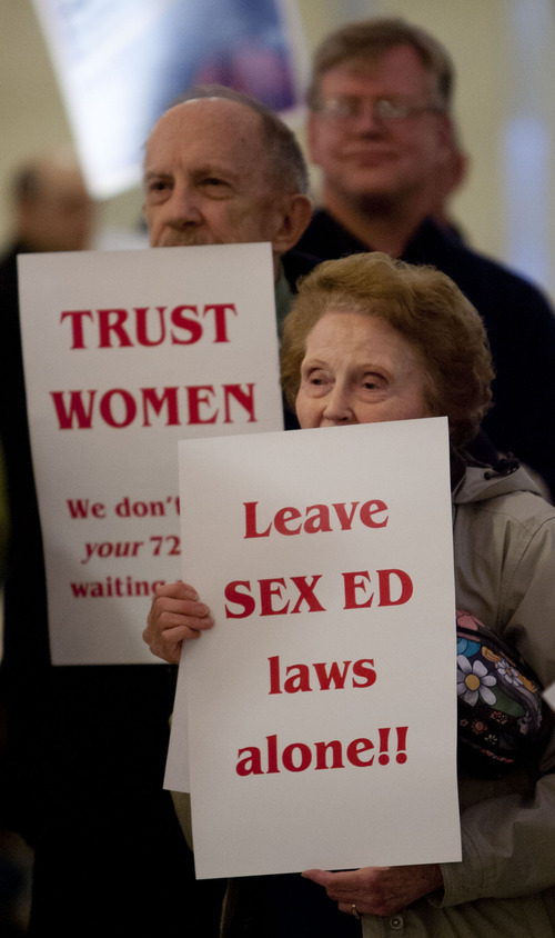 Trent Nelson  |  Tribune file photo Stuart Gygi, left, and Joyce Barnes hold up signs protesting the Legislature's action in removing a requirement for sex education in schools and moving toward imposing a 72-hour waiting period for women seeking abortions. The two were part of a