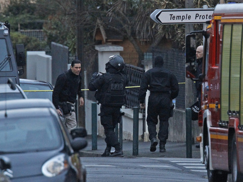 French special intervention police officers of Research Assistance Intervention Dissuasion unit, RAID, arrive at the building in Toulouse, Thursday March 22, 2012 where a suspect in the shooting at Ozar Hatorah Jewish school has been spotted. French police is prepared to storm an apartment building  to arrest a holed-up gunman who is suspected in seven killings and claiming allegiance to al-Qaida, a top police official said. (AP Photo/Remy de la Mauviniere)