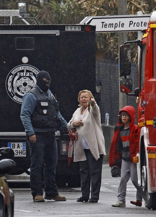 A woman speaks with a police officer near a building where the chief suspect in an al-Qaida-linked killing spree is holed up in an apartment in Toulouse, France Thursday March 22, 2012. Mohamed Merah France's chief suspect in the shooting of three Jewish schoolchildren, a rabbi, and three French paratroopers in three separate incidents wants to