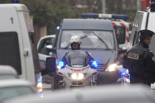 A hearse, center back, leaves the scene after a suspect wanted in the deaths of three paratroopers, three Jewish schoolchildren and a rabbi, died following a standoff with police, Toulouse, France, Thursday, March 22, 2012. Mohamed Merah, who boasted of killing seven people to strike back at France died after being shot in the head by police as he jumped out of his apartment after a fierce gunfight with police, authorities said. (AP Photo/Thibault Camus)