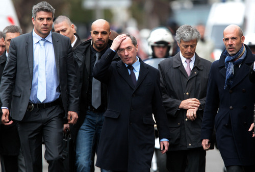 French Interior Minister Claude Gueant, center, is surrounded by police chiefs and aides as he arrive to talk to the media near an apartment where an Islamic extremist was holed up, in Toulouse, France Thursday, March 22, 2012. Mohamed Merah, who boasted of killing seven people in an attempt to
