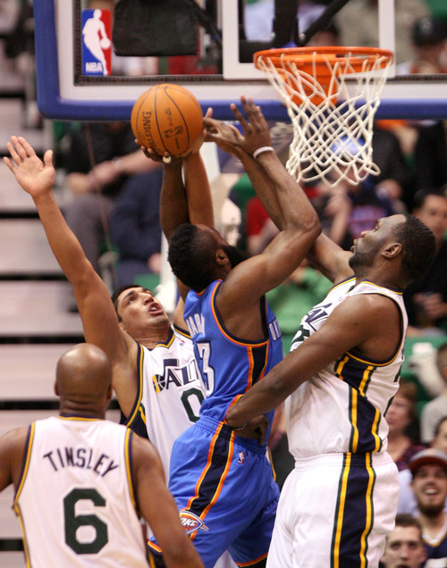 Leah Hogsten  |  The Salt Lake Tribune Jazz's Enes Kanter and Al Jefferson swat the ball out of the Thunder's James Harden.  Utah Jazz lead 52-44 after the first half against Oklahoma City Thunder, Tuesday, March 20, 2012, at the Energy Solutions Arena in Salt Lake City, Utah .