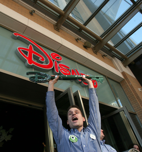 Steve Griffin  |  The Salt Lake Tribune  Austin McMullin, a cast member at the Disney Store at the City Creek Center, holds up the key to the store during the official opening of the store and the City Creek Center in Salt Lake City on Thursday, March 22, 2012.