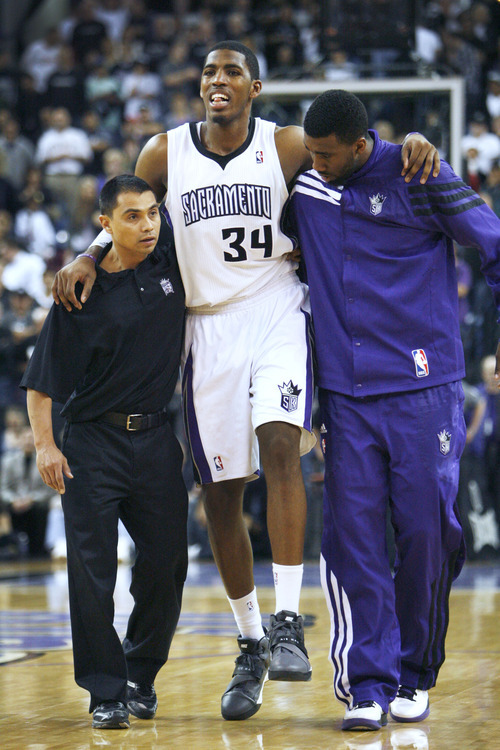 Sacramento Kings forward Jason Thompson (34) is helped off the court by teammate Donte Greene, right, and assistant trainer Manny Romero after loosing an NBA basketball game to the Utah Jazz in Sacramento, Calif., Thursday, March 22, 2012. The Jazz won 103-102.(AP Photo/Steve Yeater)