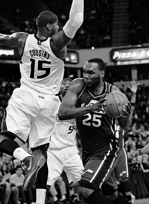 Utah Jazz center Al Jefferson (25) drives to the basket against Sacramento Kings defender DeMarcus Cousins (15) during the first half of an NBA basketball game in Sacramento, Calif., Thursday, March 22, 2012. (AP Photo/Steve Yeater)