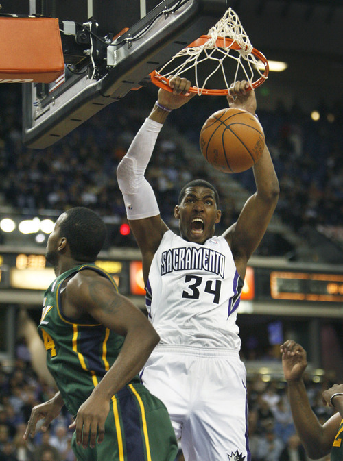 Sacramento Kings forward Jason Thompson (34) dunks over Utah Jazz defender Paul Milsap during the second half of an NBA basketball game in Sacramento, Calif., Thursday, March 22, 2012. The Jazz won 103-102.(AP Photo/Steve Yeater)