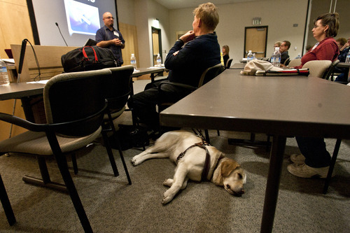 Leah Hogsten  |  The Salt Lake Tribune Leader seeing eye dog Noel rests on the floor next to her owner Jim Huber, President of the Utah chapter of the Foundation Fighting Blindness as he listens to Luis Perez. Perez, left, is a recognized Apple Distinguished Educator from the University of South Florida in Tampa, demonstrated how sight-impaired people can use Apple computers, iPads and iPhones to enhance their lives at John A. Moran Eye Center in Salt Lake City on Saturday.
