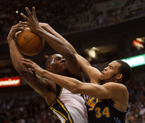 Trent Nelson  |  The Salt Lake Tribune Utah Jazz forward Derrick Favors (15) is fouled by Denver's Javale McGee. Utah Jazz vs. Denver Nuggets, NBA basketball Friday, March 23, 2012 at EnergySolutions Arena in Salt Lake City, Utah.