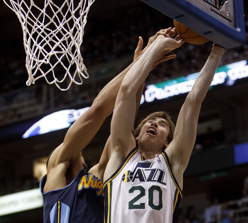 Trent Nelson  |  The Salt Lake Tribune Utah Jazz forward Gordon Hayward (20) is fouled by Denver's Javale McGee. Utah Jazz vs. Denver Nuggets, NBA basketball Friday, March 23, 2012 at EnergySolutions Arena in Salt Lake City, Utah.