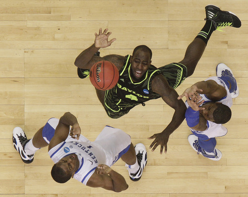 Kentucky's Marquis Teague, right, and Kentucky's Darius Miller work for a rebound with Baylor's Quincy Acy (4) during the second half of an NCAA tournament South Regional finals college basketball game Sunday, March 25, 2012, in Atlanta. (AP Photo/David J. Phillip)