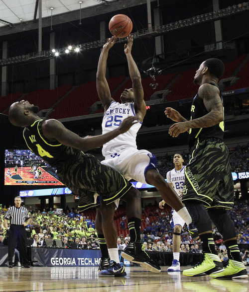 Kentucky's Marquis Teague (25) collides into Baylor's Quincy Acy (4) during the first half of an NCAA tournament South Regional finals college basketball game Sunday, March 25, 2012, in Atlanta. (AP Photo/David J. Phillip)