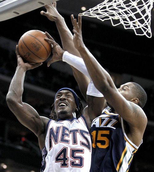 New Jersey Nets' Gerald Wallace (45) goes up for a shot against Utah Jazz's Derrick Favors (15) in the third quarter of an NBA basketball game, Monday, March 26, 2012, in Newark, N.J. The Jazz won 105-84. (AP Photo/Julio Cortez)