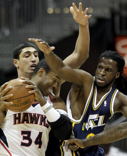 Atlanta Hawks' Jason Collins (34) defends the ball from Utah Jazz's Enes Kanter, rear, and DeMarre Carroll, right, during the second quarter of an NBA basketball game Sunday, March 25, 2012, in Atlanta. (AP Photo/David Goldman)