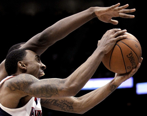 Atlanta Hawks' Jeff Teague puts up a shot under the reach of Utah Jazz's Al Jefferson during the third overtime of an NBA basketball game Sunday, March 25, 2012, in Atlanta. Atlanta won 139-133 in four overtimes. (AP Photo/David Goldman)
