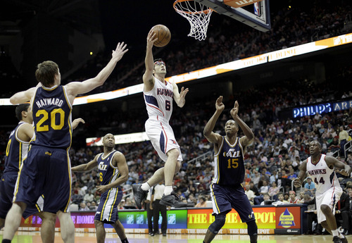 Atlanta Hawks' Kirk Hinrich (6) puts up a basket between Utah Jazz' Gordon Hayward (20) and Derrick Favors during triple overtime of an NBA basketball game, Sunday, March 25, 2012, in Atlanta. Atlanta won 139-133 in the NBA's first quadruple-overtime game since 1997. (AP Photo/David Goldman)