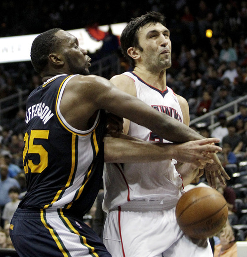 Utah Jazz's Al Jefferson, left, fouls Atlanta Hawks center Zaza Pachulia, of Georgia, during triple overtime of an NBA basketball game, Sunday, March 25, 2012, in Atlanta. Atlanta won 139-133 in the NBA's first quadruple-overtime game since 1997. (AP Photo/David Goldman)