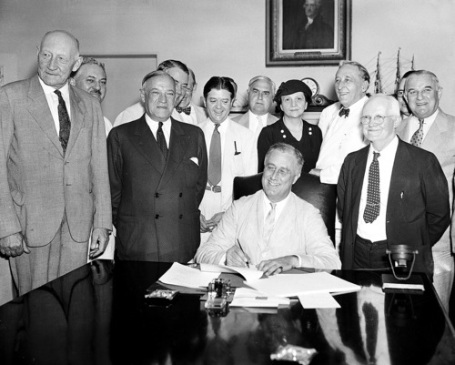 FILE - In this Aug. 14, 1935, file photo President Franklin Roosevelt signs the Social Security Bill in Washington. In 1935 Americans struggle to pay for medical care amid the Great Depression. Roosevelt favors creating national health insurance, but decides to push for Social Security first. He never gets the health program passed. But his Social Security bill will provide old age pensions and unemployment insurance. From left are: Chairman Doughton of the House Ways and Means Committee; Sen. Wagner, D-N.Y, co-author of the bill, Secretary Perkins, Chairman Harrison of the Senate Finance Committee, Rep. Lewis, D-Md., co-author of the measure. (AP Photo/File)