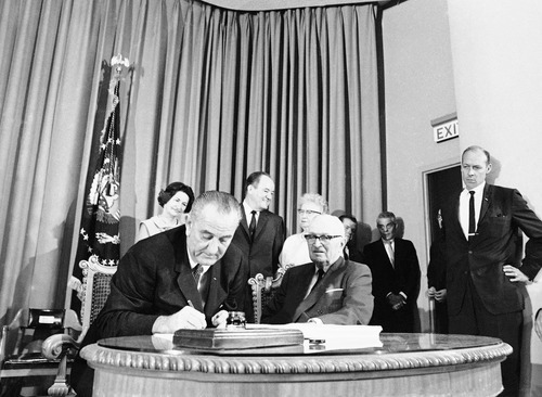 FILE - In this July 30, 1965, file photo President Lyndon B. Johnson, left, with former Pres. Harry S. Truman at his side, uses the last of many pens to complete the signing of the Medicare Bill into law at ceremonies at the Truman Library in Independence, Missouri. John signed Medicare for people age 65 and older and Medicaid for the poor into law. His legendary arm-twisting and a Congress dominated by his fellow Democrats succeeded in creating the kind of landmark health care programs that eluded his predecessors. At rear from left are Lady Bird Johnson, Vice President Hubert Humphrey, and former first lady Bess Truman.  (AP Photo/File)
