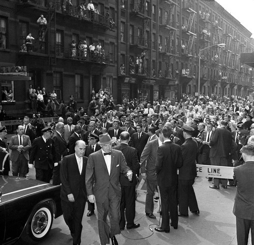 FILE - In this May 20, 1962, file photo Midtown Manhattan residents line the fire escapes to watch President John F. Kennedy, at center above man with hat in foreground, walk along West 49th Street in New York under a cordon of police and Secret Servicemen, as he make his way to Madison Square Garden to address a rally in support of his administration's Medicare program for the elderly. Though he made health care a major campaign issue, as president he can't get a plan for the elderly through Congress. (AP Photo/File)