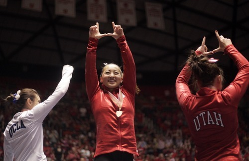 Kim Raff | The Salt Lake Tribune University of Utah gymnast Corrie Lothrop gives the U of U symbol after winning the best all around for the competition during the Pac 12 Gymnastics Championship at the Huntsman Center in Salt Lake City, Utah on March 24, 2012.