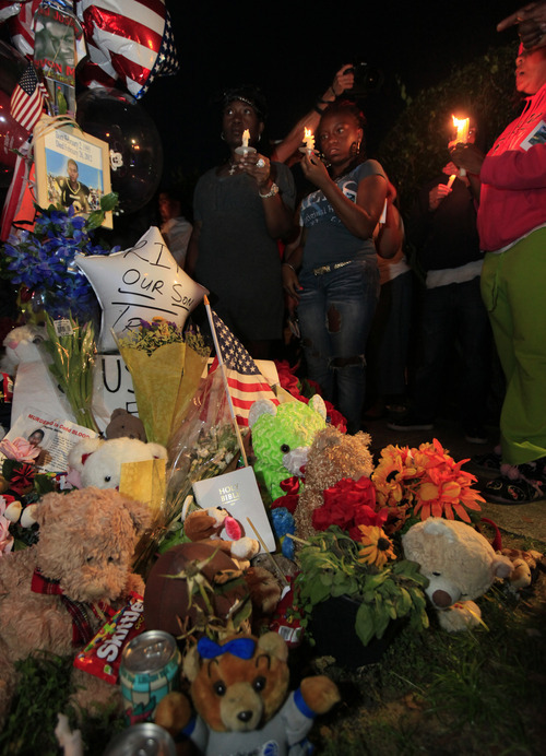 Crowds gather for the candlelight vigil at the memorial outside the Retreat at Twin Lakes, where Trayvon Martin was shot by neighborhood watch captain George Zimmerman, in Sanford, Fla., Sunday, March 25, 2012. (AP Photo/Julie Fletcher)