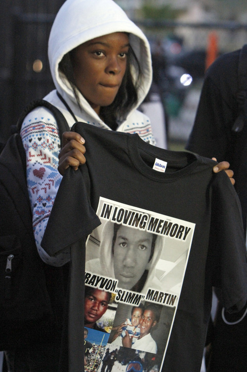Walter Michot  |  The Miami Herald via AP Francesca Placide, a student at Michael Krop High School displays her black t-shirt in tribute to Trayvon Martin, Monday, March 26, 2012, in Miami. There have been rallies around the country as anger has spread over the shooting a month ago of Martin, 17, who  died after neighborhood watch captain George Zimmerman reported him to police as suspicious and then followed him.