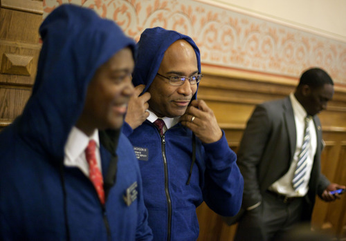 Sen. Lester G. Jackson, III, D-Savannah, right, puts his hoodie on as he leaves the  Georgia Senate floor with Sen. Emanuel Jones, D-Decatur, left, to join a rally outside the statehouse in memory of Trayvon Martin, the unarmed 17-year-old who was killed by a Florida neighborhood watch captain, Monday, March 26, 2012, in Atlanta. (AP Photo/David Goldman)