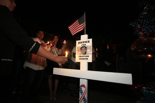 A woman holds a candle near a cross placed at the memorial site during the candlelight vigil service held outside the gates of the Retreat at Twin Lakes, where Trayvon Martin was shot by neighborhood watch volunteer George Zimmerman, in Sanford, Fla., Sunday, March 25, 2012.  (AP Photo/Julie Fletcher)