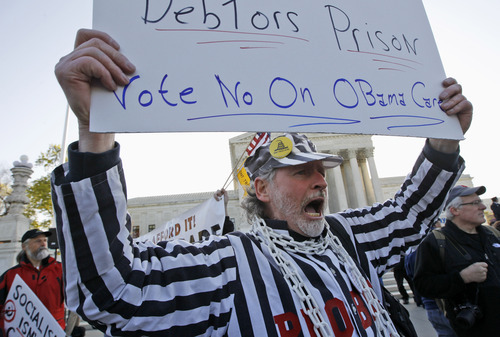 Michael Wade, from East Brookfield, Mass., who opposes health care reform, rallies in front of the Supreme Court in Washington, Tuesday, March 27, 2012, as the court continues arguments on the health care law signed by President Barack Obama. (AP Photo/Charles Dharapak)