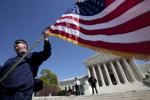 Holding an American flag and a copy of the Constitution, Dan, who asked not to use his last name, of Virginia, protests against the health care law, Monday, March 26, 2012, outside of the Supreme Court in Washington after the first day of arguments on President Obama's health care legislation. (AP Photo/Jacquelyn Martin)