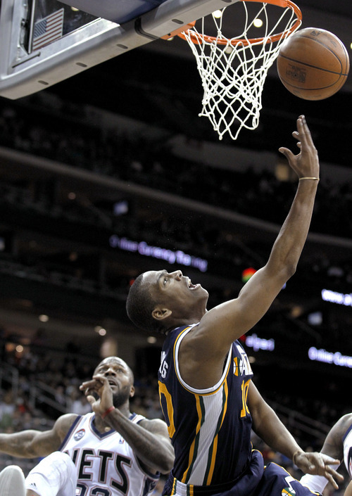 Utah Jazz's Alec Burks, right, goes up for a layup as New Jersey Nets' DeShawn Stevenson watches during the second quarter of an NBA basketball game, Monday, March 26, 2012, in Newark, N.J. (AP Photo/Julio Cortez)