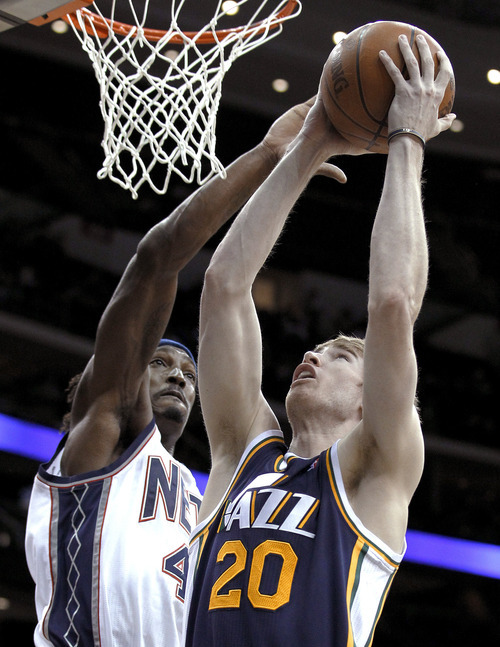 Utah Jazz's Gordon Hayward, right, goes up for a shot against New Jersey Nets' Gerald Wallace in the second quarter of an NBA basketball game, Monday, March 26, 2012, in Newark, N.J. (AP Photo/Julio Cortez)