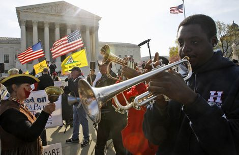 Jonathan Neal, a senior at Howard University, plays his trumpet in support of health care reform in front of the Supreme Court in Washington, Wednesday, March 28, 2012, on the final day of arguments regarding the health care law signed by President Barack Obama. (AP Photo/Charles Dharapak)