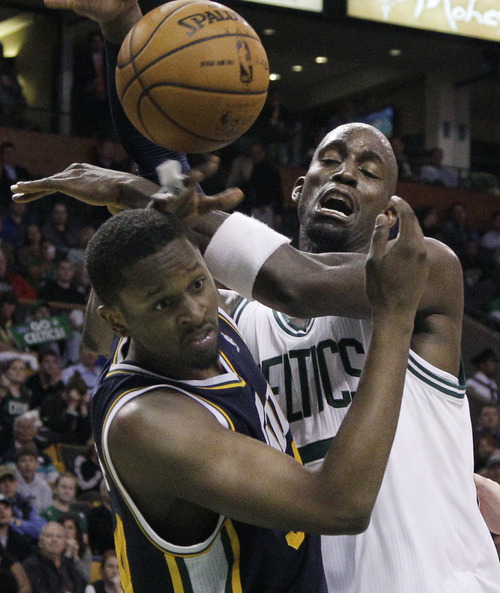 Elise Amendola     The Associated Press  Utah Jazz forward C.J. Miles, left, and Boston Celtics forward Kevin Garnett scramble for a loose ball in the second half of an NBA basketball game in Boston on Wednesday.