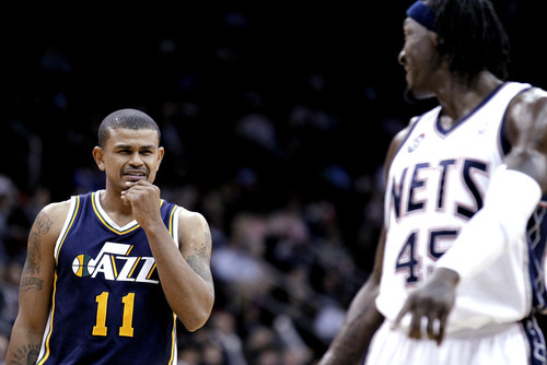Utah Jazz's Earl Watson (11) talks to New Jersey Nets' Gerald Wallace during the third quarter of an NBA basketball game, Monday, March 26, 2012, in Newark, N.J. The Jazz won 105-84. (AP Photo/Julio Cortez)