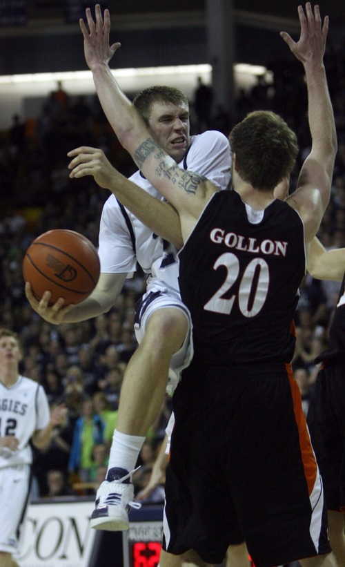 Kim Raff | The Salt Lake Tribune Utah State University player Morgan Grim drives the basket as he is defended by Mercer player Jakob Gollon during the CIT Championship game at Utah State University in Logan, Utah on March 28, 2012.  Mercer went on to win the game 67-70.