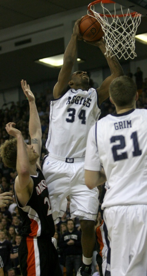 Kim Raff | The Salt Lake Tribune Utah State University player Kyisean Reed goes up for a shot over the head of and Mercer player Jakob Gollon during the CIT Championship game at Utah State University in Logan, Utah on March 28, 2012.