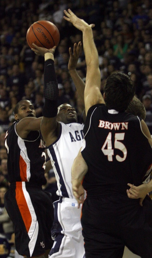 Kim Raff | The Salt Lake Tribune Utah State University player Brockeith Pane takes a shot as he is defended by Mercer players (left) Langston Hall and Monty Brown during the CIT Championship game at Utah State University in Logan, Utah on March 28, 2012.  Mercer went on to win the game 67-70.