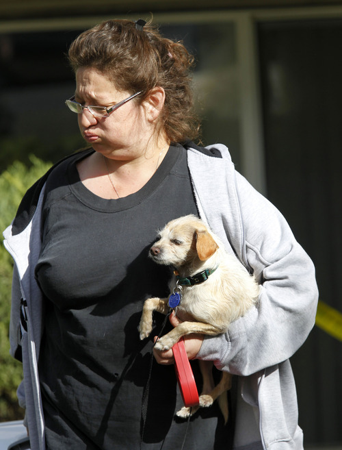 Al Hartmann  |  The Salt Lake Tribune It was a long night and morning for renters at an apartment complex at 400 North and Redwood Road. Unidentififed renter takes her dog Thursday morning from the smoke-damaged apartment building.