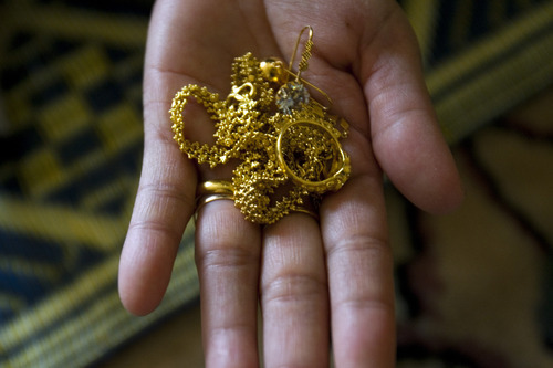 Chris Detrick  |  The Salt Lake Tribune Pearlly Wa shows some of her daughter Hser Ner Moo's jewelry in their apartment on Wednesday. Hser Ner Moo was killed on March 31, 2008. She wore this gold jewelry from Thailand on her last visit to church before she died.