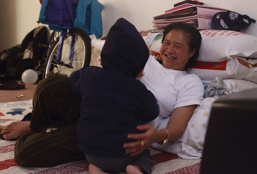 Photo by Leah Hogsten     The Salt Lake Tribune Above, Pearlly Wa  plays with her youngest child Eh Ler Wah, 1,  in their modest apartment in Marshalltown, IA in 2009. Burmese immigrants Cartoon Wah, 49 and his wife Pearlly Wa, 43, who once lived in Salt Lake City had moved to Marshalltown, IA, trying to leave the painful memories behind since the death of their 7-year-old daughter Hser Ner Moo. They have since returned to Utah.