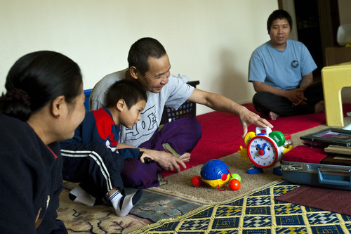 Chris Detrick  |  The Salt Lake Tribune Pearlly Wa, Eh Ler Wah, 4, Cartoon Wah and KerKer Po, 24, play with some of Hser Ner Moo's old toys in their apartment Wednesday March 28, 2012. Hser Ner Moo was killed on March 31, 2008.