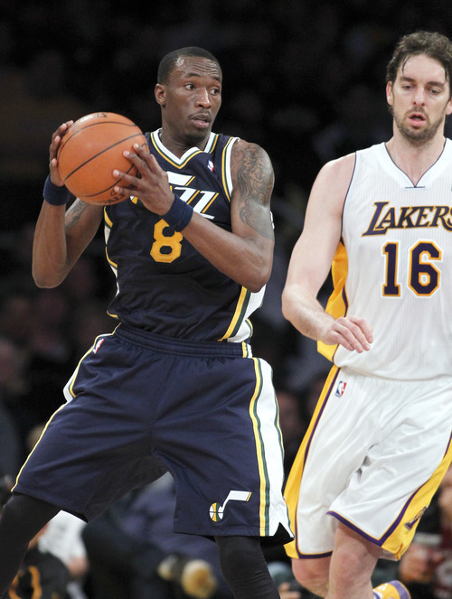 Utah Jazz forward Josh Howard (8) holds onto the ball with Los Angeles Lakers forward Pau Gasol (16), of Spain, defending during the first half of an NBA basketball game in Los Angeles, Sunday, March 18, 2012. (AP Photo/Alex Gallardo)