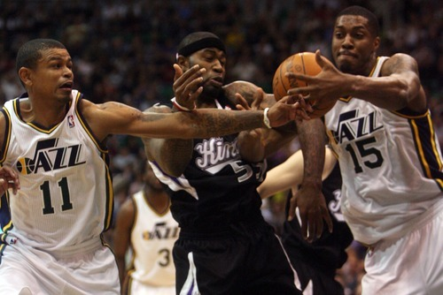 Kim Raff | The Salt Lake Tribune Jazz players (left) Earl Watson and Derrick Favors battle Kings player Terrence Williams for a rebound during a game at EnergySolutions Arena in Salt Lake City, Utah on March 30, 2012. The Jazz went on to lose the game 103-104.