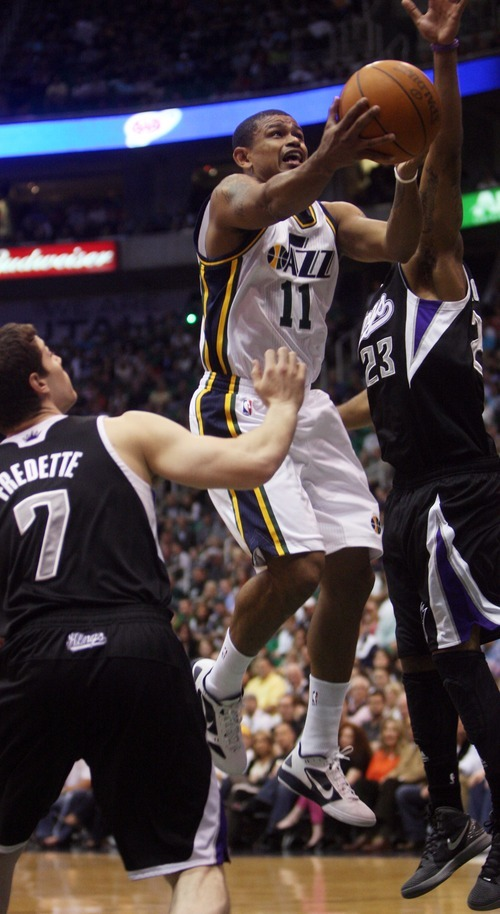 Kim Raff | The Salt Lake Tribune Jazz player Earl Watson  attempts a layup as Kings players Marcus Thornton and Jimmer Fredette defend during at game at EnergySolutions Arena in Salt Lake City, Utah on March 30, 2012.
