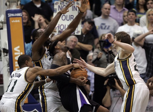 Kim Raff | The Salt Lake Tribune Jazz players (from left) Earl Watson, Al Jefferson, and Gordon Hayward put pressure on Kings player Demarcus Cousins  during a game at EnergySolutions Arena in Salt Lake City, Utah on March 30, 2012. The Jazz went on to lose the game 103-104.
