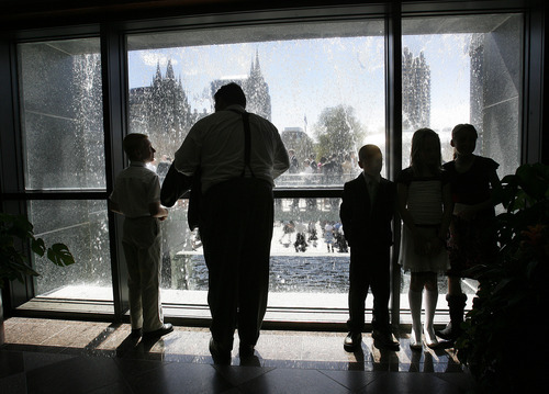 Scott Sommerdorf  |  The Salt Lake Tribune              People attending conference take in the view through the Conference Center waterfall as others wait in line to attend the afternoon session of the 182nd Annual General Conference of The Church of Jesus Christ of Latter-day Saints on Saturday.