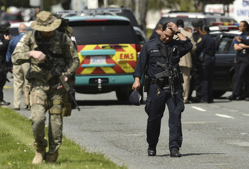 An Oakland police officer walks outside of Oikos University in Oakland, Calif., Monday, April 2, 2012. A suspect was detained Monday in a shooting attack at a California Christian university that sources said has left at least five people dead. (AP Photo/Noah Berger)
