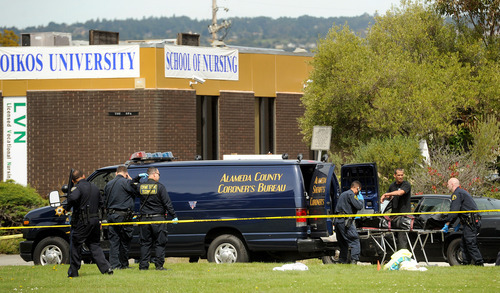 Sheriff's deputies remove a body from outside Oikos University in Oakland, Calif., Monday, April 2, 2012. A gunman opened fire at the Christian university, killing at least seven people and wounding three more, before being captured hours later at a shopping center in a nearby city, authorities said. (AP Photo/Noah Berger)