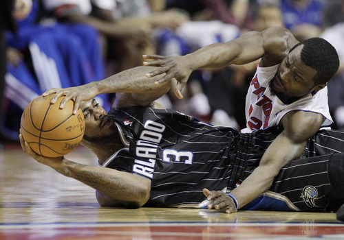 Detroit Pistons guard Will Bynum (12) and Orlando Magic forward Earl Clark (3) vie for a loose ball during the second half of an NBA basketball game at the Palace in Auburn Hills, Mich., Tuesday, April 3, 2012. (AP Photo/Carlos Osorio)